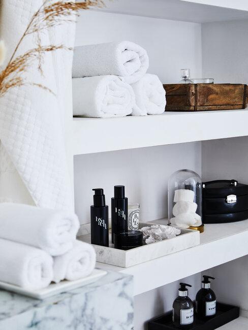 estanerias blancas con toallas y frascos negros en un baño