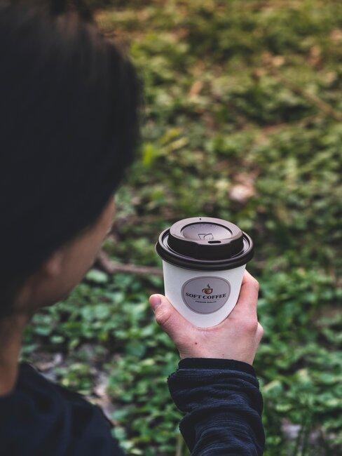 hombre lleva taza de café para llevar