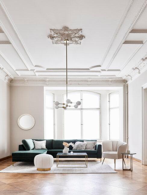 salón de techos altos con sofá verde y sillón blanco