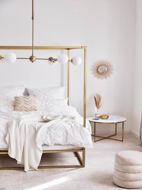 dormitorio con cama dorada y mesita dorada y blanca
