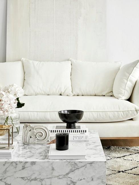 pared y sofá blanco con mesita de café de mármol