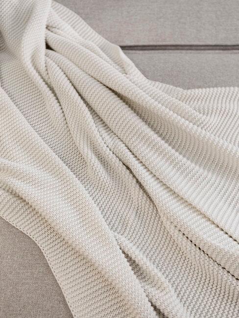 manta blanca sobre sofá beige