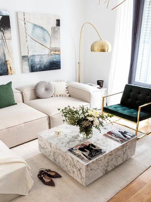 mesa de mármol con sofá beige y sillón verde