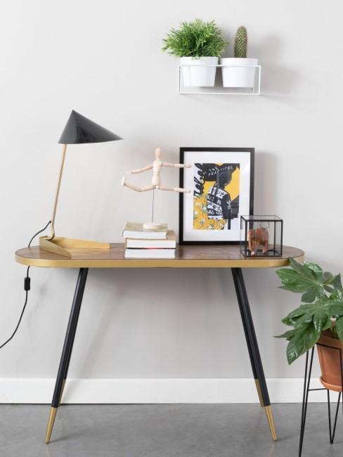 Mesa escritorio ovalado con una lampara dorada y negra