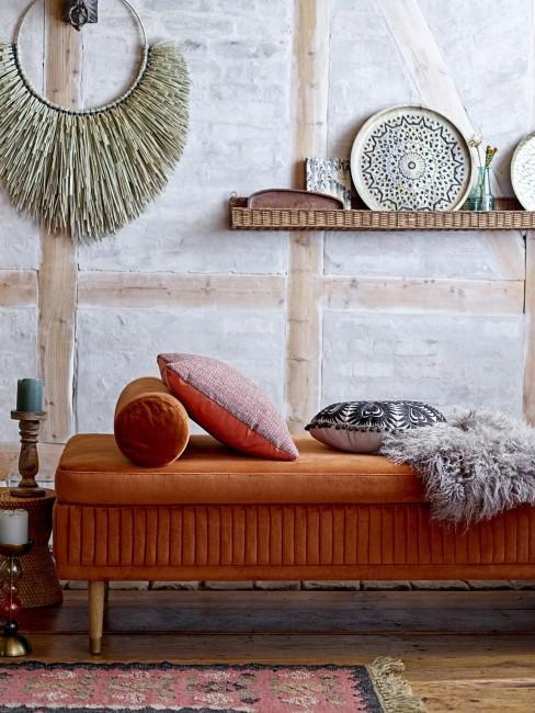 Divan naranja y pared decorada con diferentes estilos