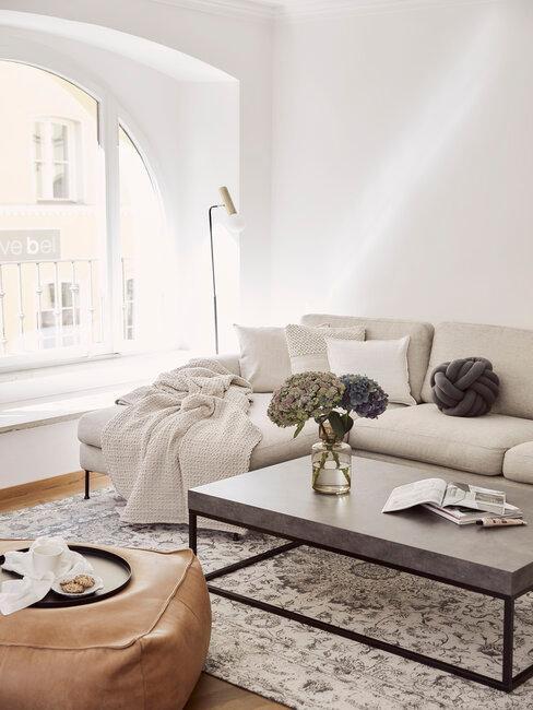 sofa beige con mesa gris y puf de cuero
