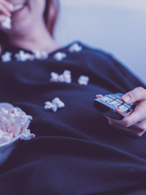 chica viendo peliculas con el mando a distancia y palomitas