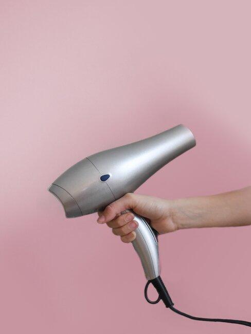 secador gris sobre fondo rosa
