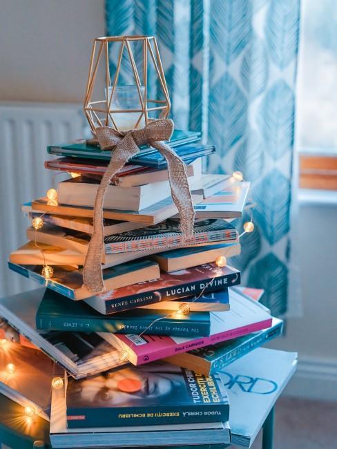Montaña de libros con una vela en la cima