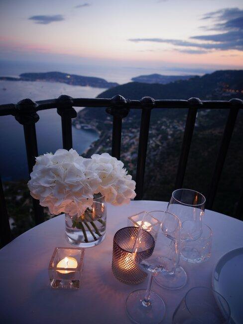mesa blanca con flores en terraza al atardecer