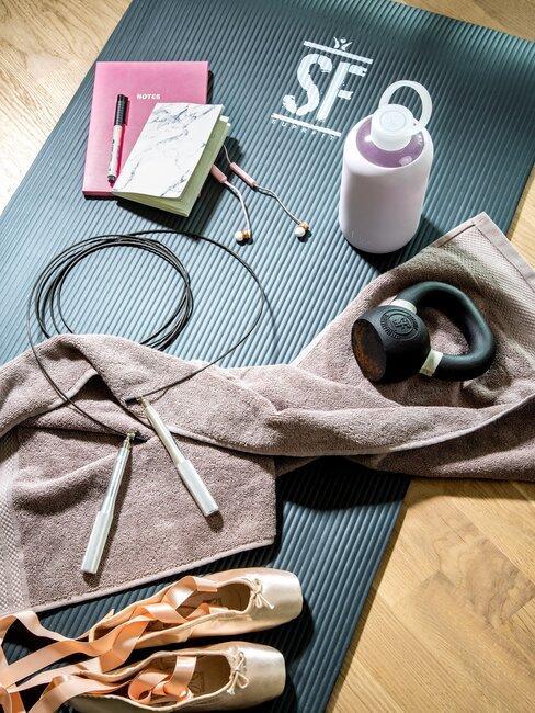 esterilla con toalla libros zapatillas y productos gimnasio