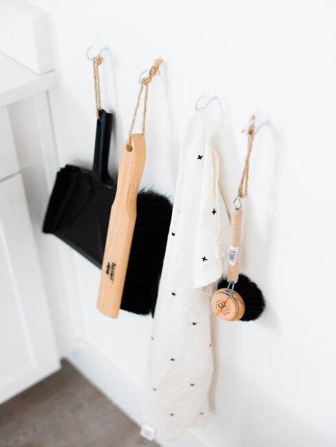 accesorios de limpieza de madera y negors colgados pared