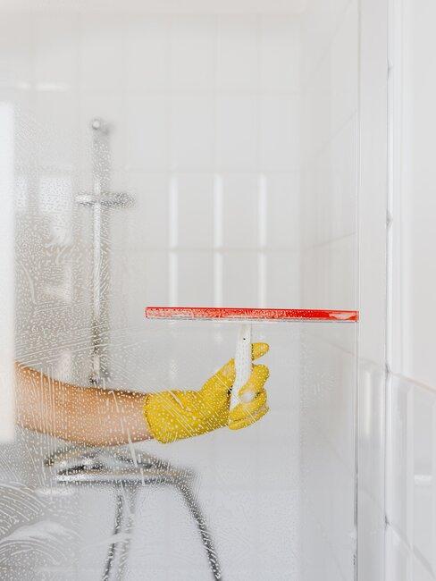 mano con guante amarillo limpia cristal mampara de ducha