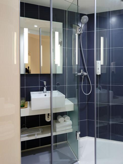 Un baño azul con una mampara de ducha transparente