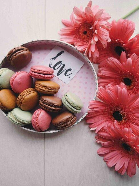 caja de macarons y flores rosas