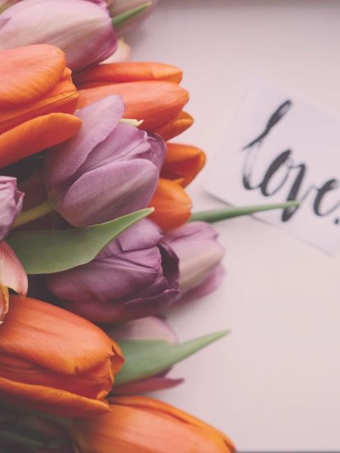 Un ramo de tulipanes con una carta que pone Love