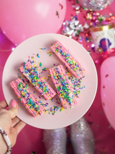 Un plato con pasteles rosas