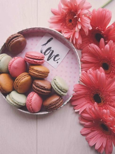 Una bandeja con macarones y flores rosas