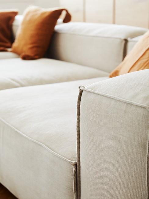sofá greige y cojin naranja