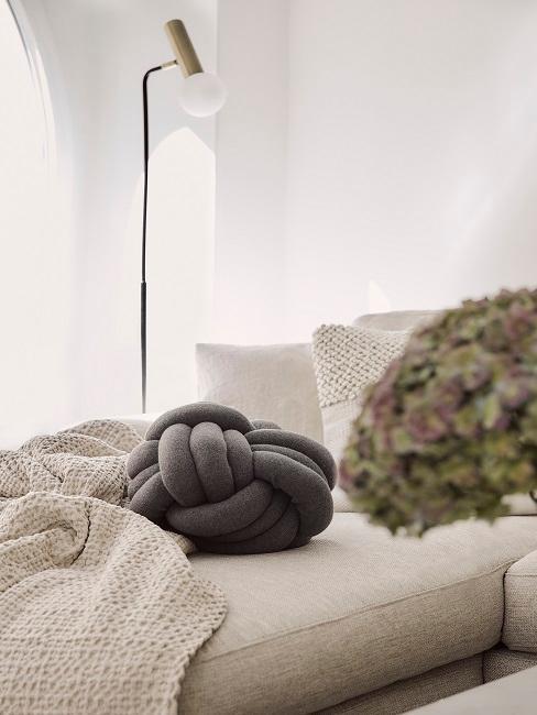 cojín gris sobre sofá greige