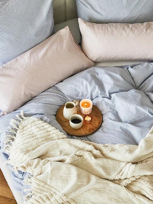 sábanas de rayas azul y rosa con manta greige y desayuno