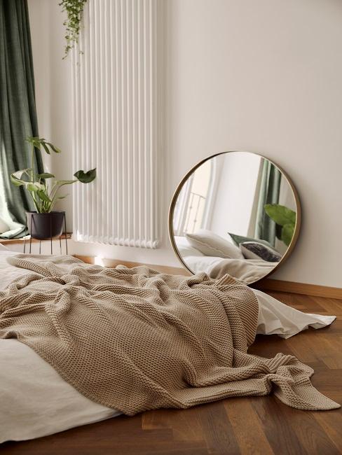 dormitorio boho con colores beige blanco y espejo redondo