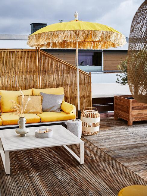 terraza en amarillo con sombrilla mesa y sofá separador de mimbre