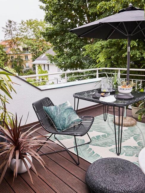 terraza con muebles negros alfombra y plantas