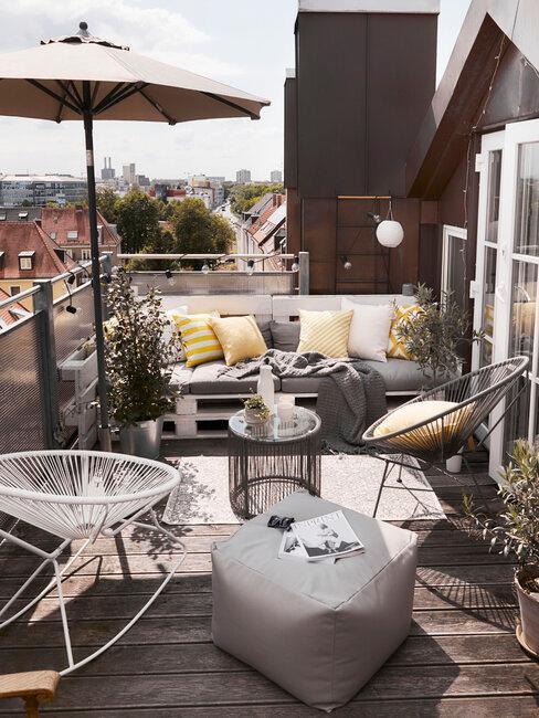 terraza con muebles y decoración gris y amarillo con sombrilla y sofá palets