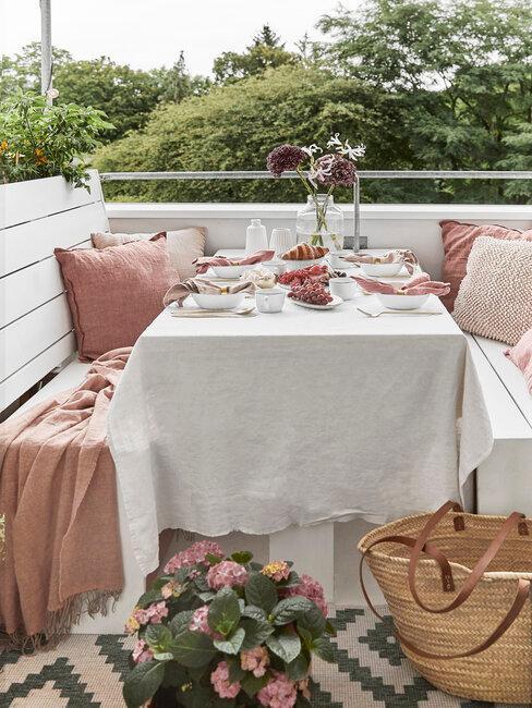 terraza con bancos blancos y mesa alfombra y flores