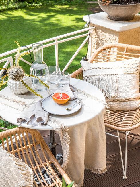 mesa redonda y sillas de mimbre en terraza