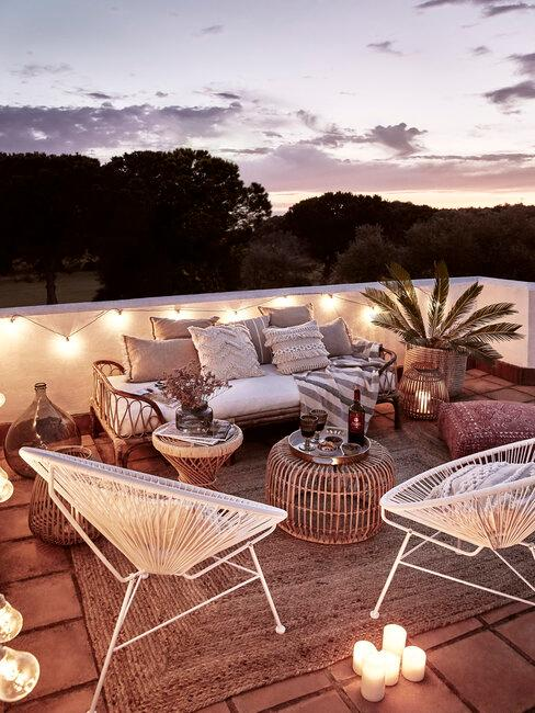 terraza iluminada con farolillos y velas muebles de mimbre y alfombra