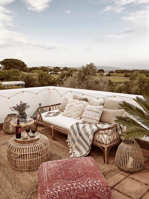 terraza con miebles de mimbre y puf