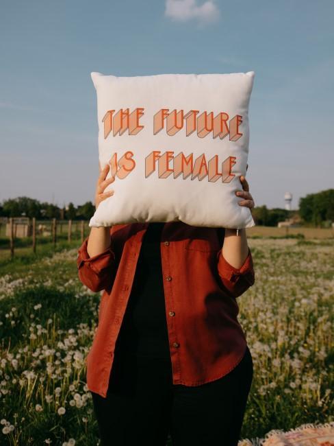 Mujer con un cojín con eslogan feminista