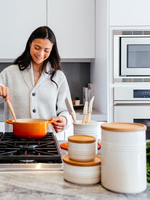Mujer cocinando en una cocina blanca