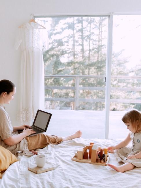 Madre trabajando en la cama con su hija
