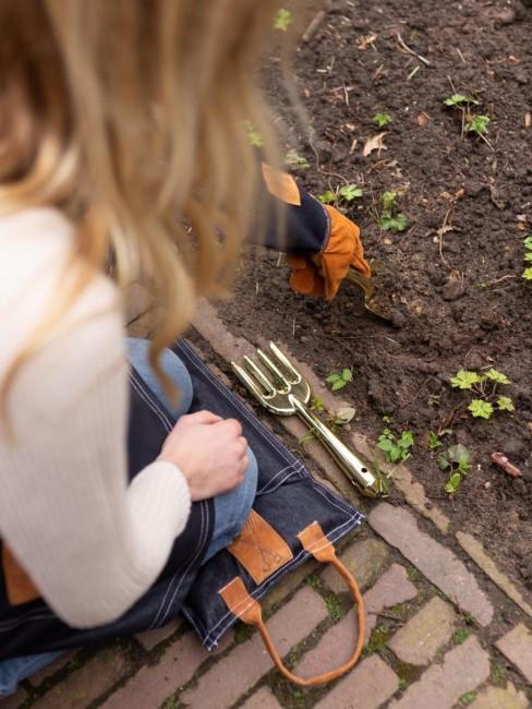 Chica con guantes arreglando el jardín