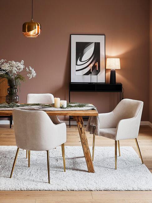 pared marrón con mesa de madera sillas de terciopelo beige flores y lámparas
