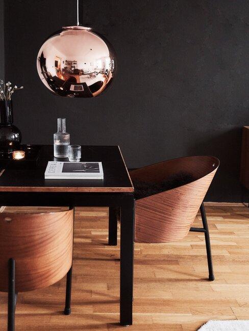 pared y mesa negra sillas de madera y lámpara cobre