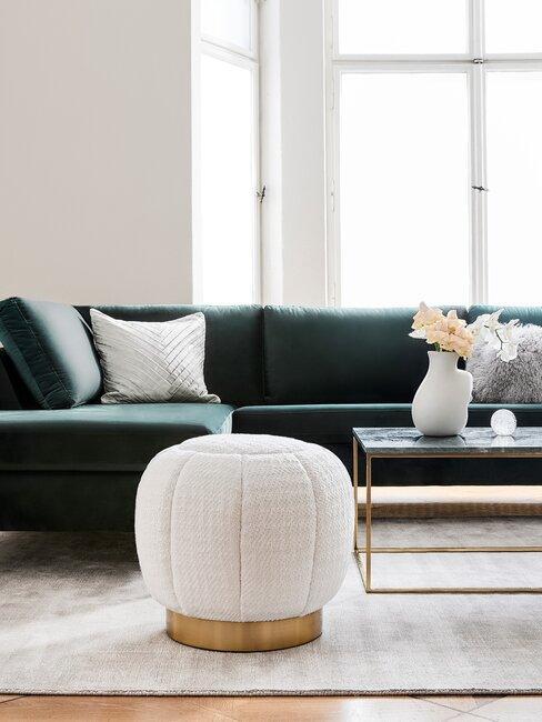 salón con sofá verde paredes alfombra y puff blanco