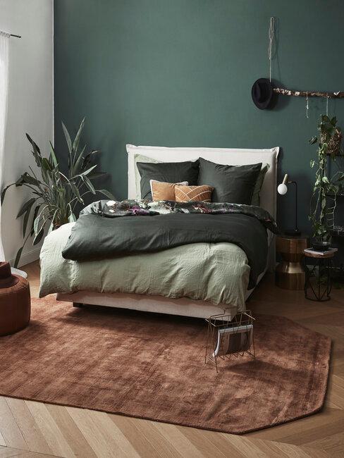 dormitorio con pared y sabánas verde oscuro cama beige alfombra marrón y planta