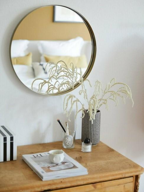 Comoda con un espejo de pared y un florero
