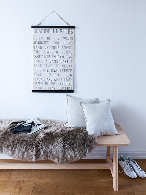 banco de madera con pieles cojines y decoración de pared
