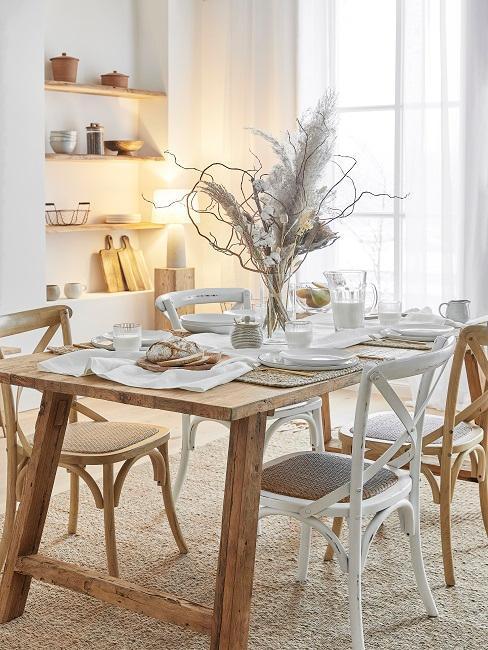 comedor con mesa y sillas de madera natural y blanco flores secas