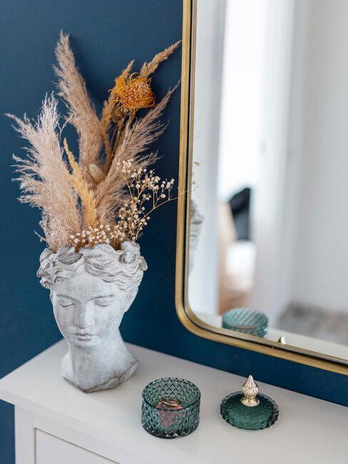 macetero con forma de cabeza de mujer con plantas secas