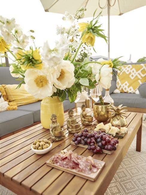 Mesa de exterior decorada con flores y con comida