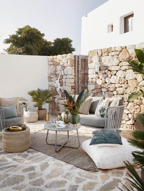 Terraza decorada con cojines y con una pared de piedras