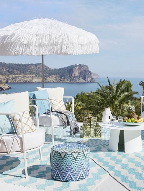 Terraza con sombrilla blanca con vistas al mar
