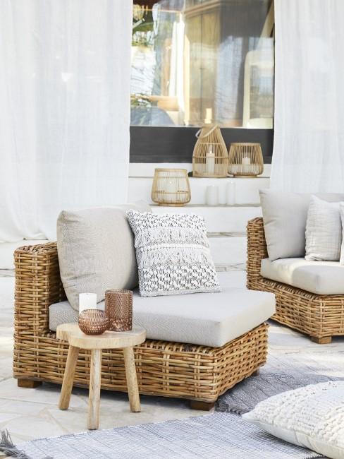 Terraza con un sillón de mimbre y cortinas