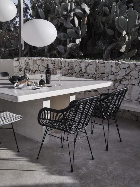 Terraza con una mesa de comedor y sillas negras